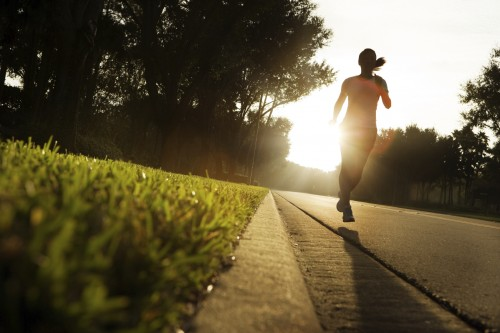 young woman running on rural road at sunrise